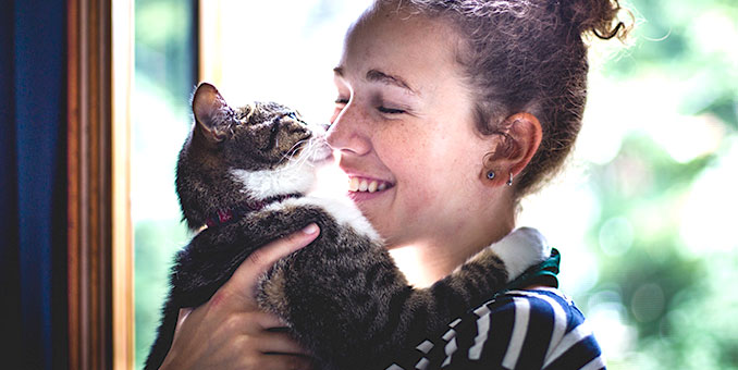 young girl hugging cat